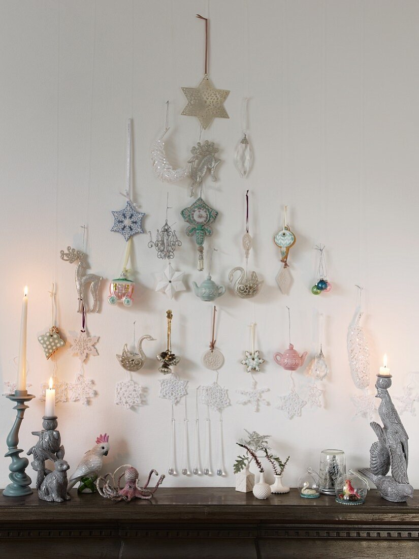 Pastel-coloured Christmas tree baubles hung in the shape of a Christmas tree over a chest of drawers with ceramic figurines