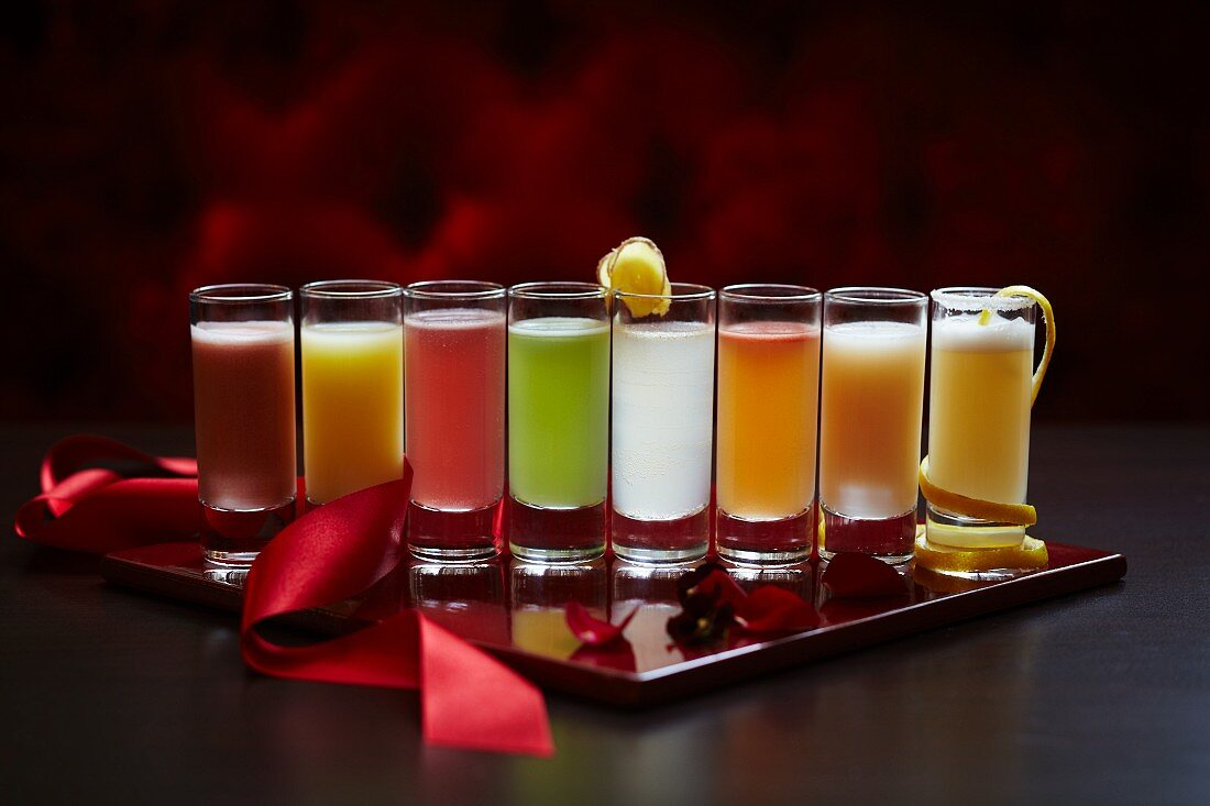 A row of shot glasses filled with different coloured cocktail