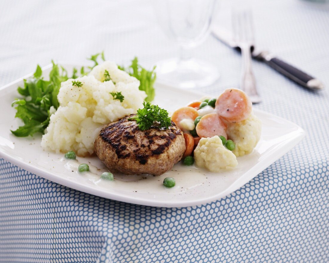 A meat patty with creamy vegetables and mashed cauliflower