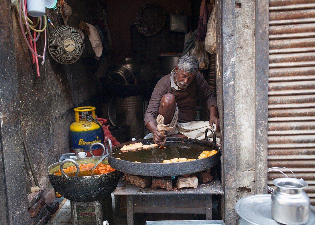 A street vendor preparing Jalebi (deep-fried rings, India)