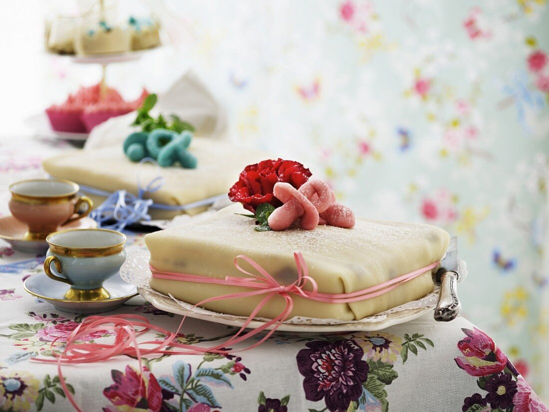 Two cakes for a pair of twins decorated with pink and light blue marzipan dummies