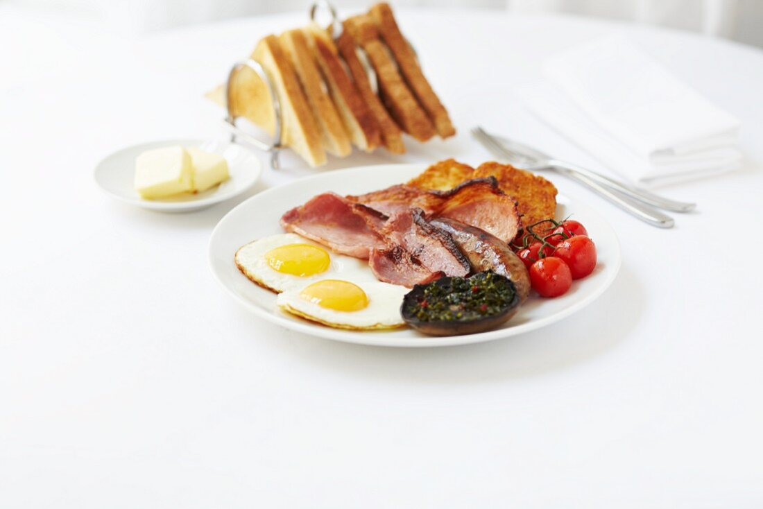 Breakfast of fried eggs, bacon, sausages, fried mushrooms, hash browns and tomatoes served with a rack of toast