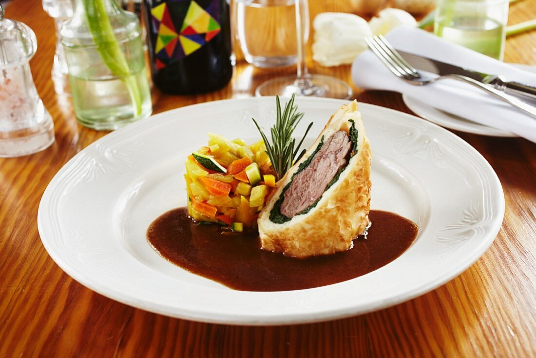 Saddle of lamb with spinach wrapped in strudel pastry and served with vegetables