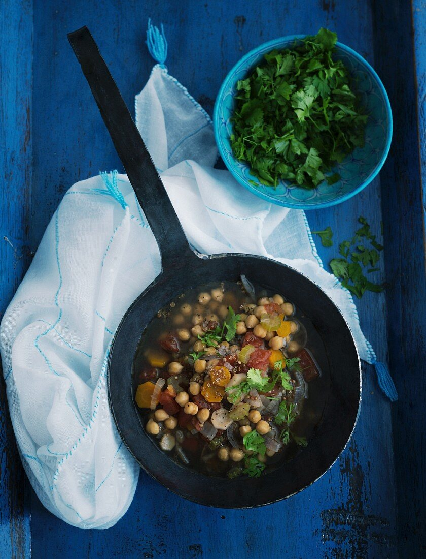 Beef stock with chickpeas and vegetables in a black pan on a blue wooden surface