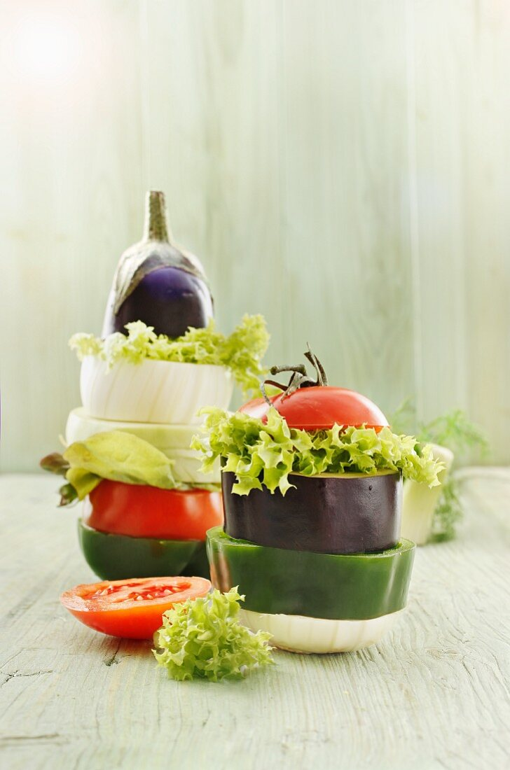 Stacks of vegetables with onions, peppers, aubergines, salad and tomatoes