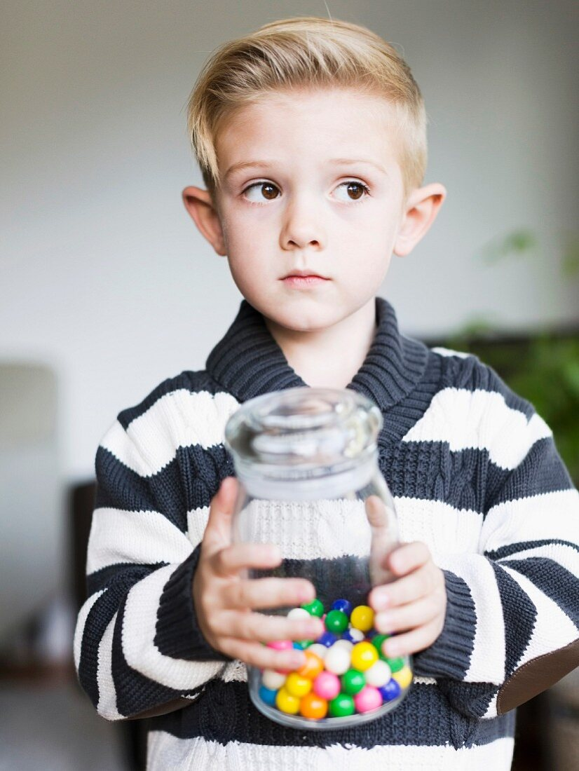 A boy holding a jar of bonbons