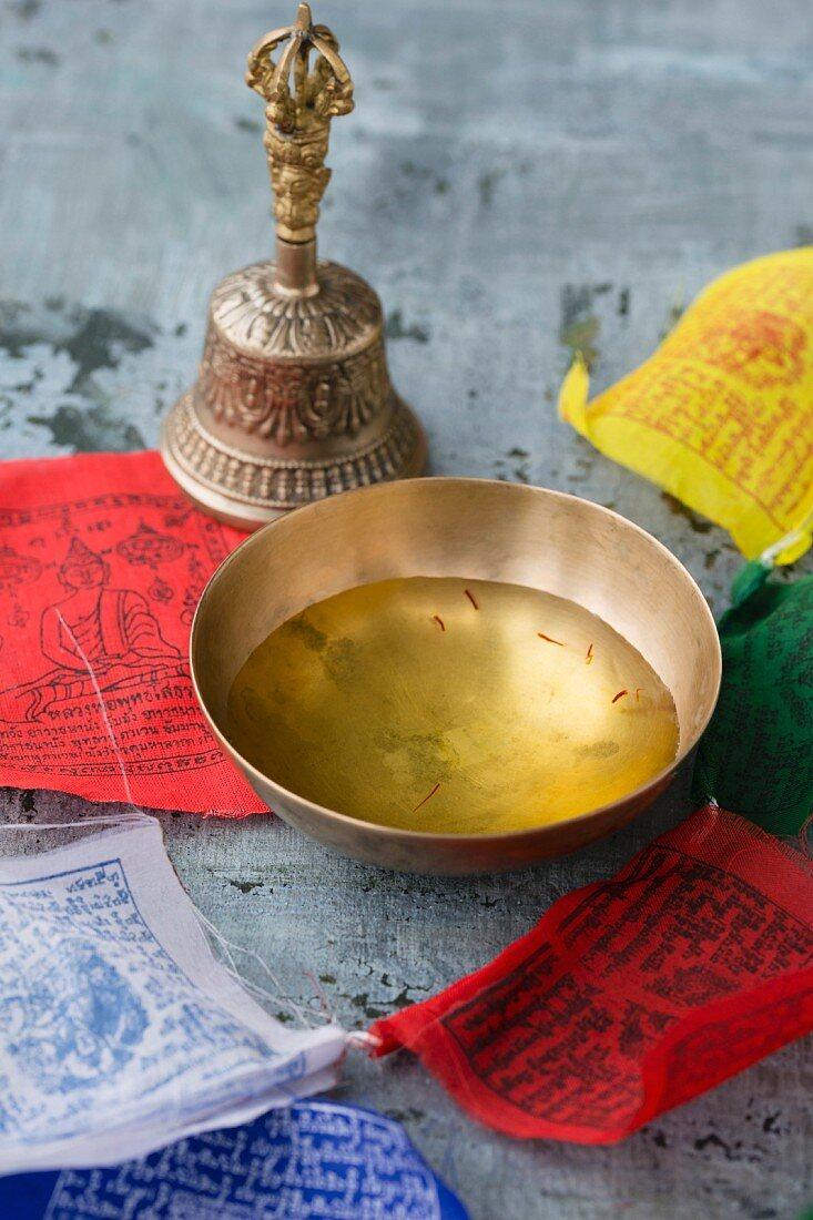 A bowl of saffron water, a Tibetian bell and prayer flags