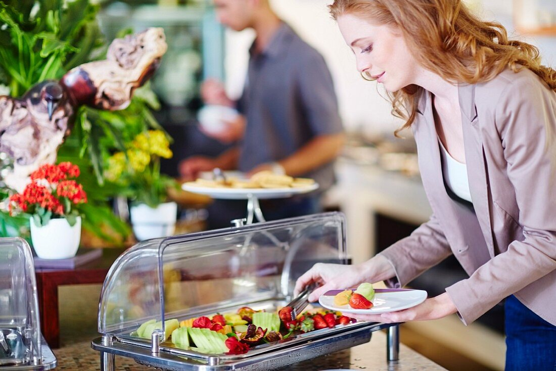 A businesswoman taking fruit from a salad bar