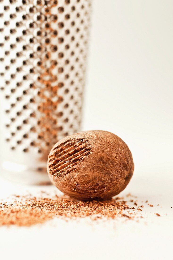 A whole nutmeg with a grater