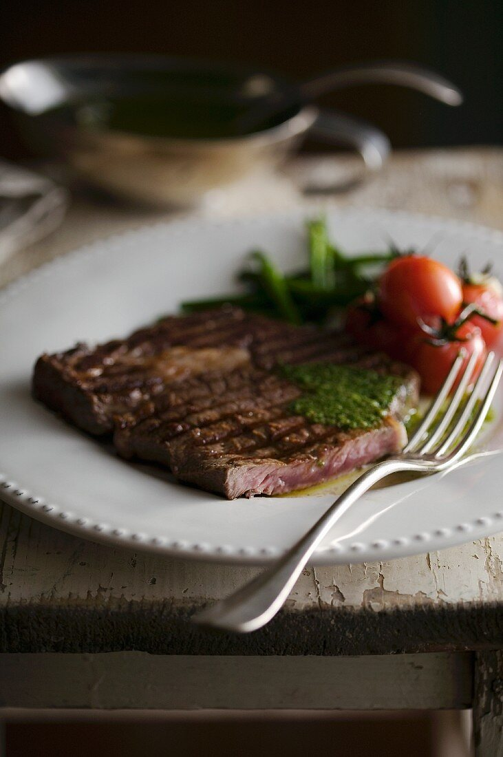 Grilled rib-eye steak with a herb sauce
