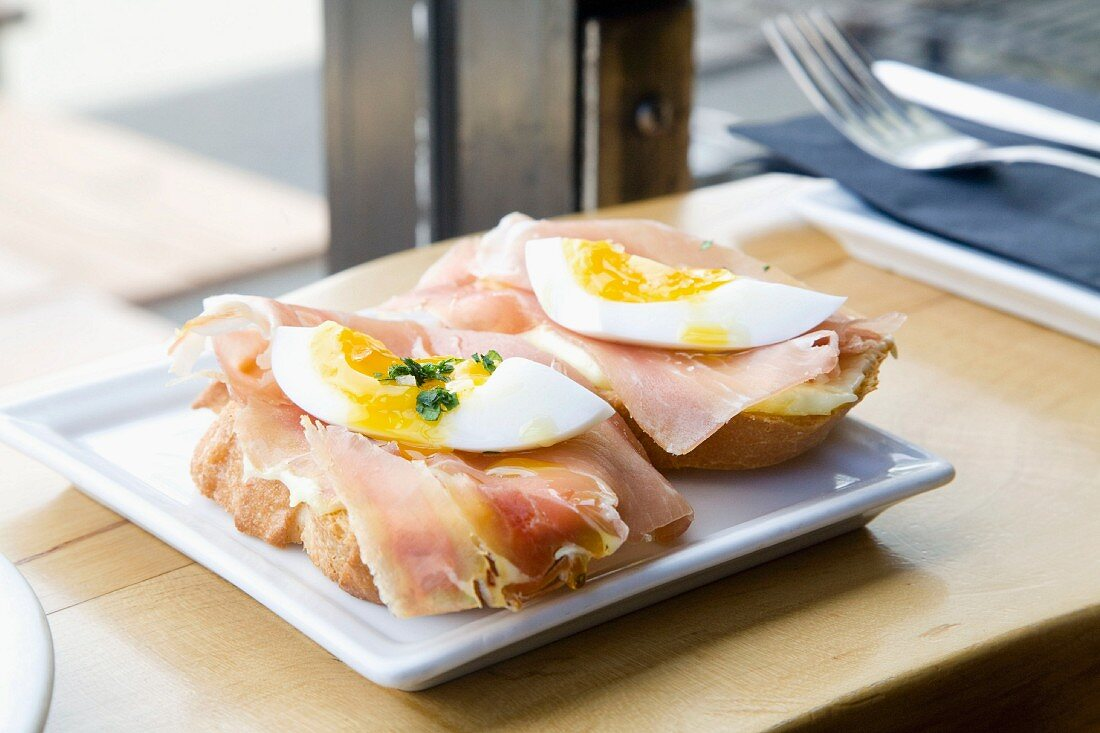 Slices of bread topped with ham and soft-boiled egg