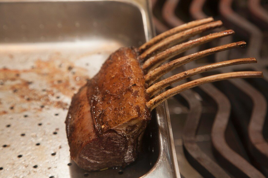 Roast rack of lamb ribs in a stainless steel container