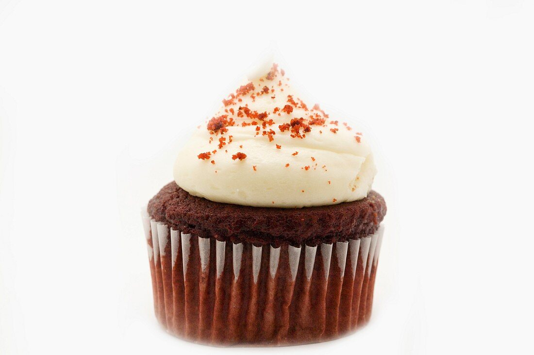 A Red Velvet cupcake decorated with cream and crumbs