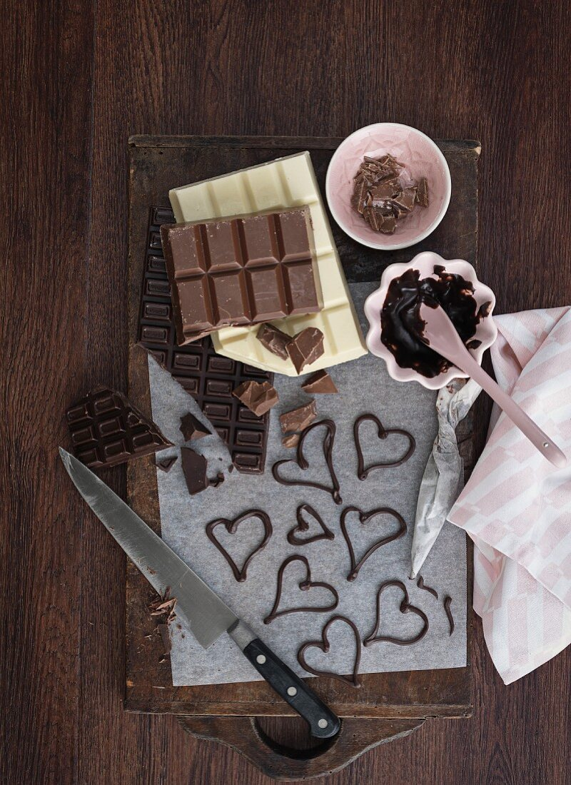 Various chocolate bars, melted chocolate and chocolate hearts