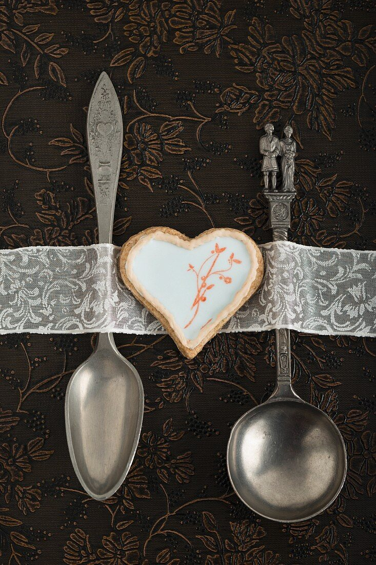 A heart-shaped biscuit decorated with egg white glaze and a stamped motif between wedding-themed spoons