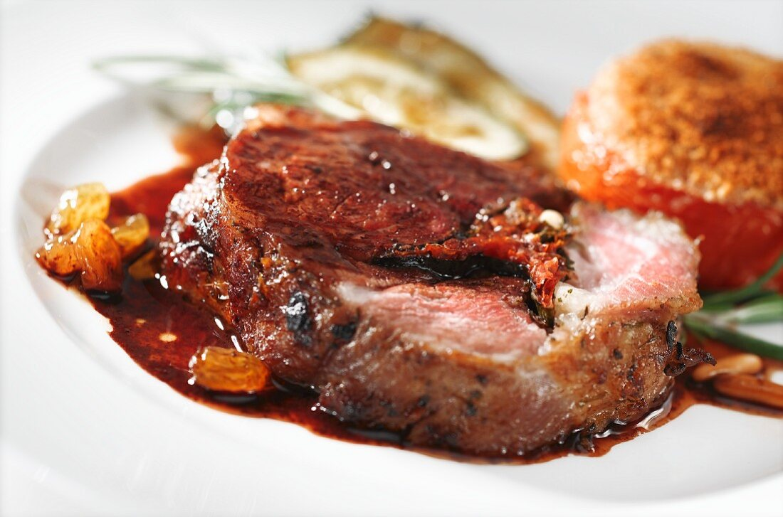 Roast lamb with raisin sauce and stuffed tomatoes