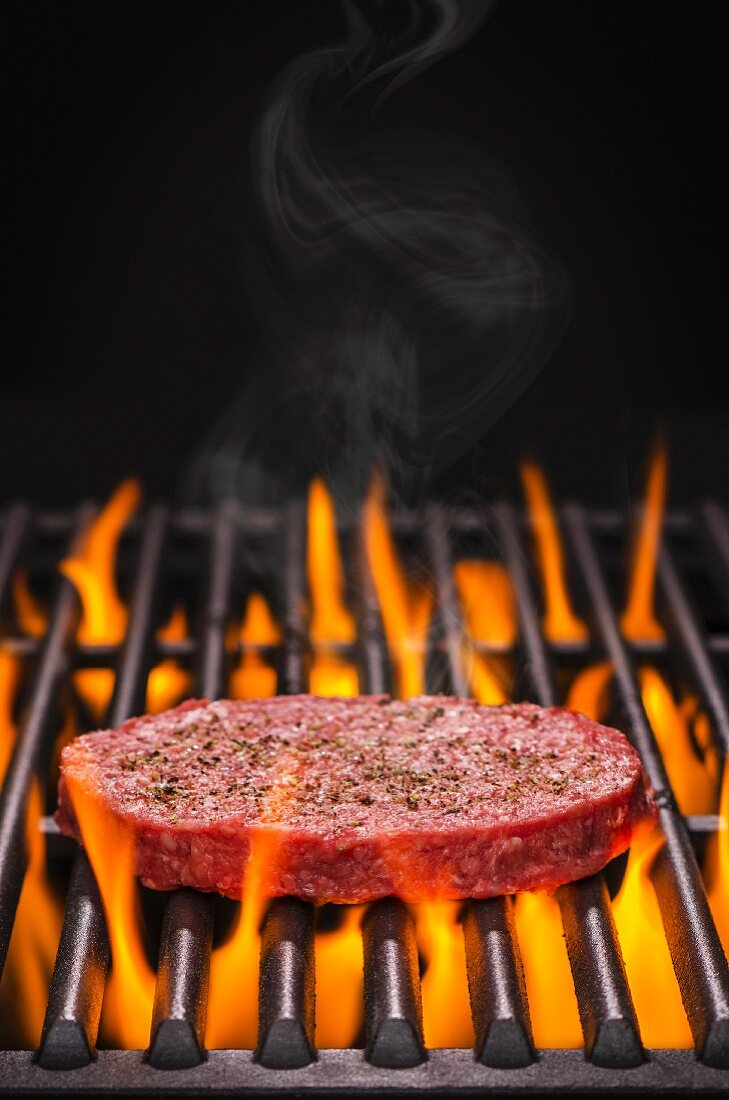 A raw hamburger with salt and pepper on a flaming barbecue