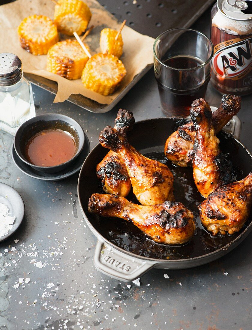 Barbecue chicken legs and grilled corn cobs in a diner