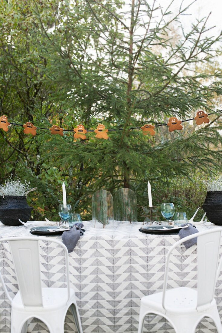 A winter table laid outside with garlands of gingerbread men