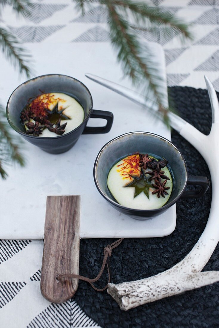 Mulled wine in cups with slices of apples, saffron and star anise