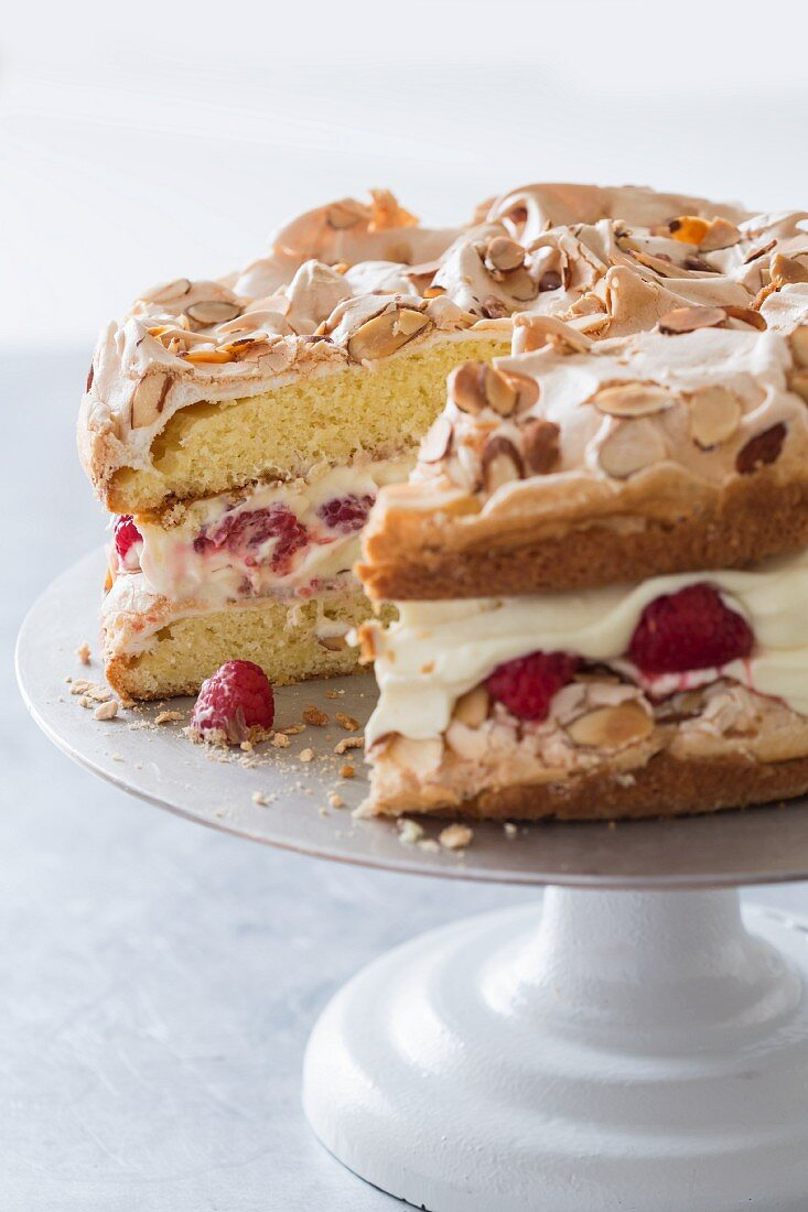 Quick cake made from sponge cake, cream and raspberries with a meringue topping on a cake stand