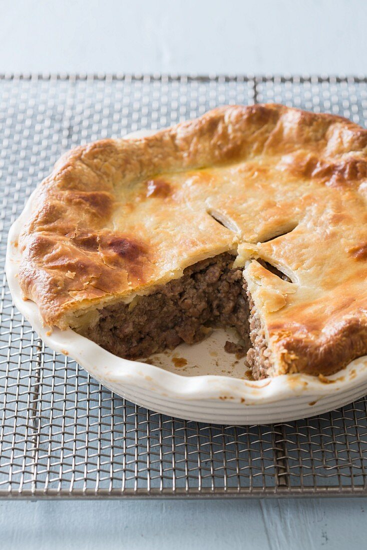 Tourtiere (French-Canadian meat pie) in a baking dish on a wire rack with a slice cut out