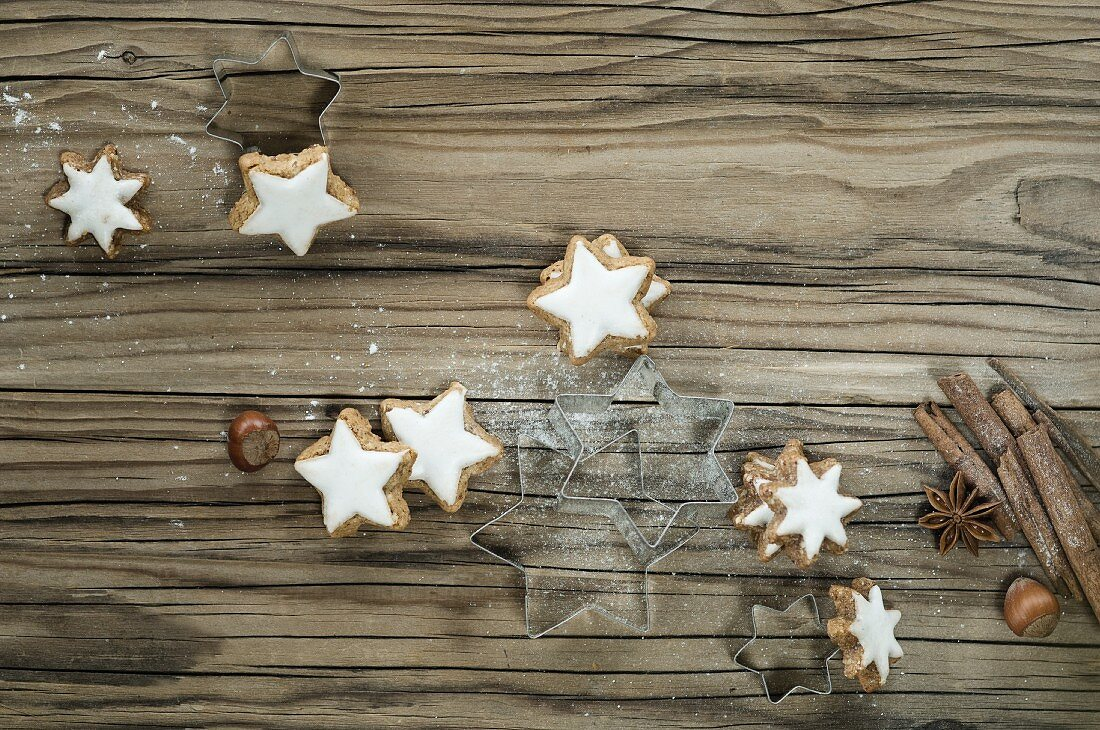 Biscuit cutters, cinnamon stars and cinnamon sticks on the wooden surface
