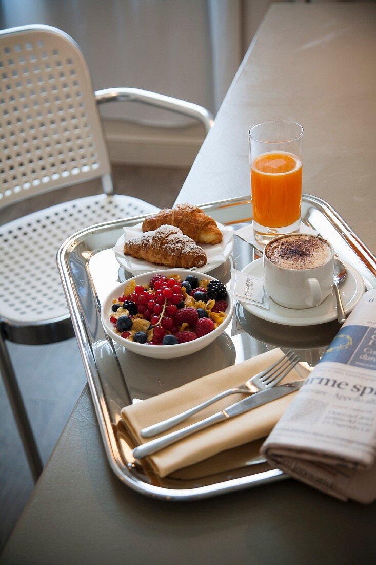 Breakfast with croissants, cappuccino, orange juice and cereal with fresh berries
