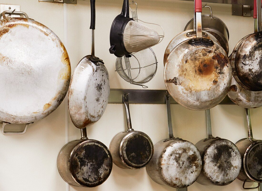Pots, pans and kitchen utensils hanging on a wall
