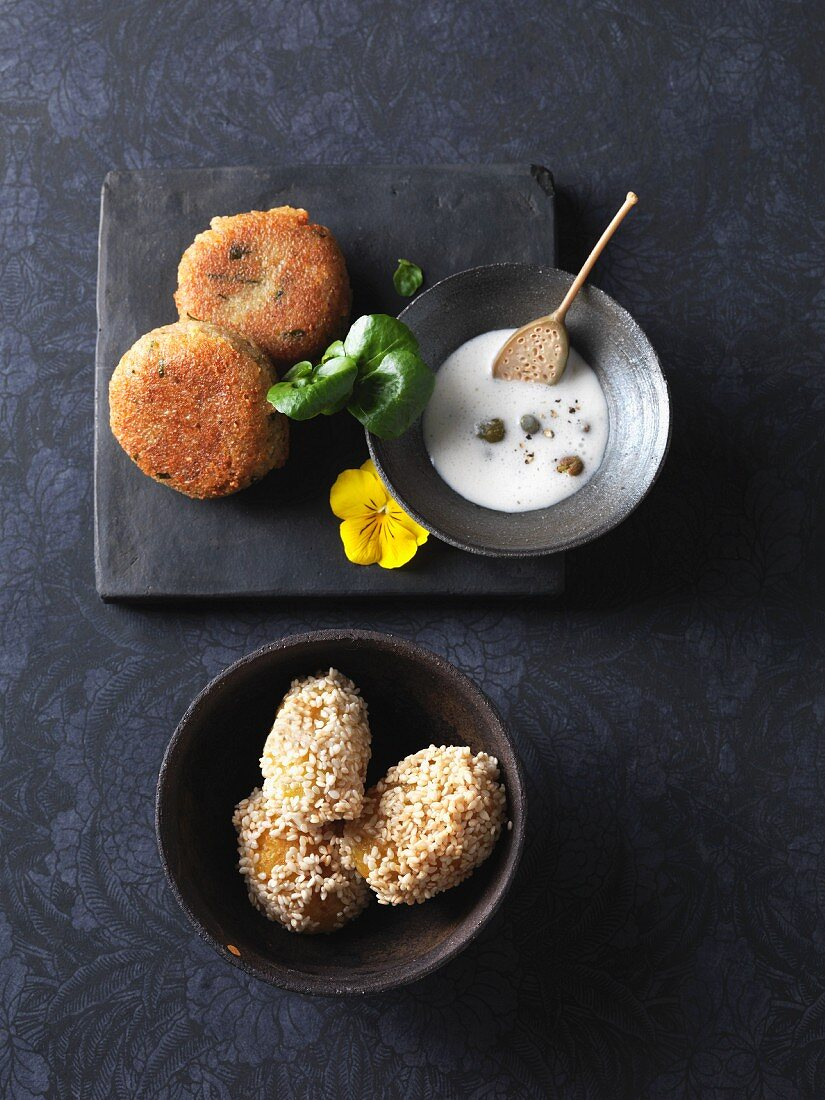 Caper sauce served with vegetarian green spelt fritters and sesame seed potatoes