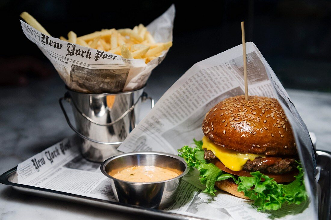 A hamburger with fries and a dip wrapped in newspaper on a tray