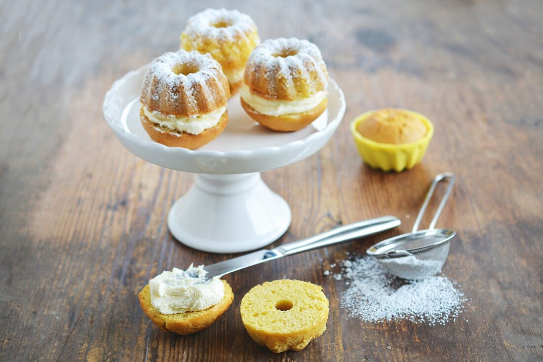 A mini Bundt cake with cream and icing sugar on a cake stand