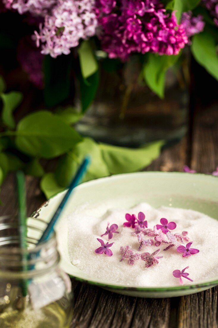 Lilac flowers being candied in sugar