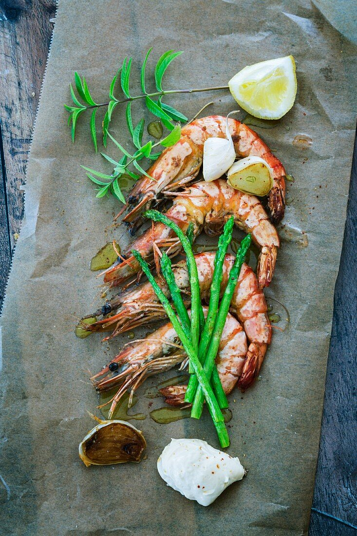 Prawns with garlic, asparagus and mayonnaise on a piece of baking paper