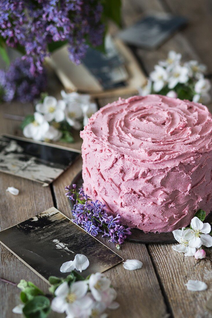 A spring birthday cake covered with pink frosting on a wooden surface with flowers and old photographs