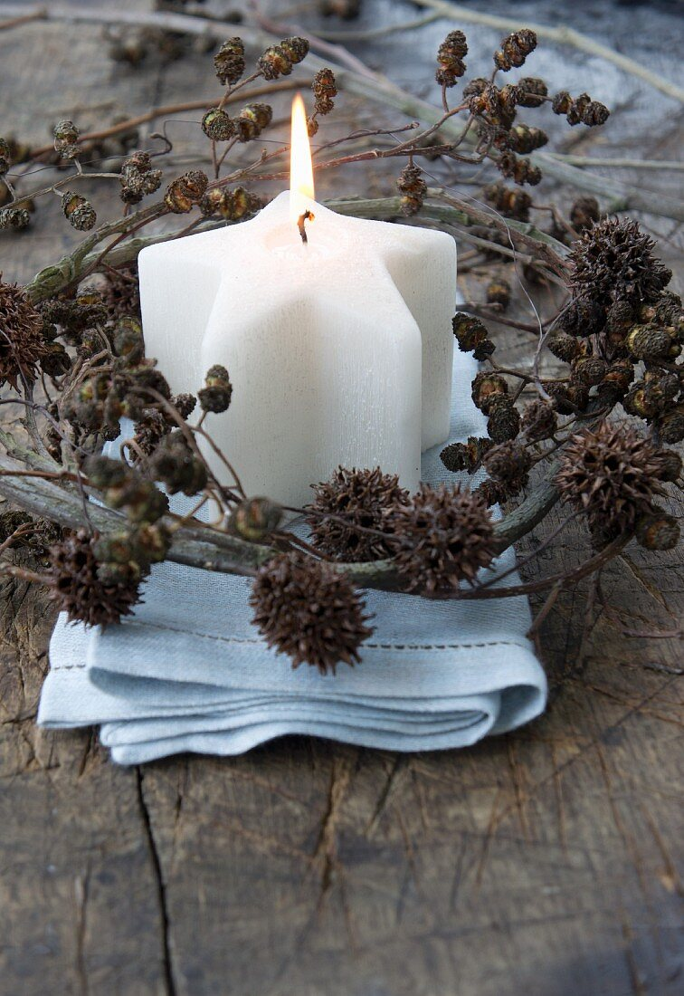 A star-shaped candle with a wreath of alderberry and maple fruit sprigs