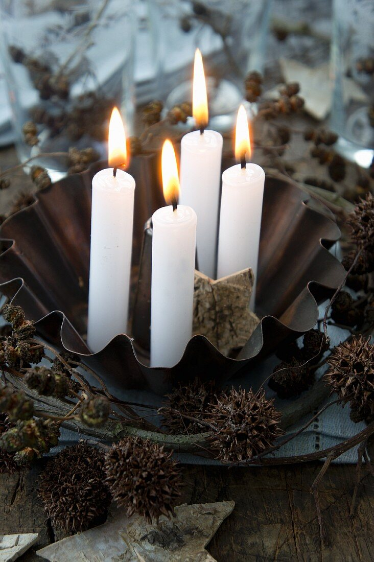 Vier Kerzen in einer Backform mit einem Kranz aus Erlen und Ahornfruchtständen