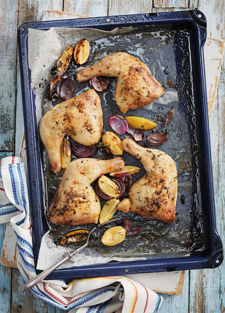 Roast chicken legs with lemons and red onions on a baking tray