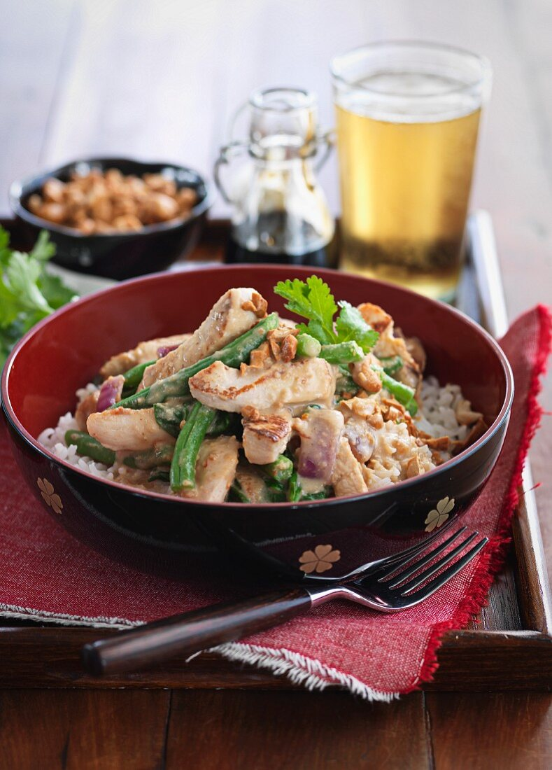 Satay chicken with peanut sauce, beans and rice