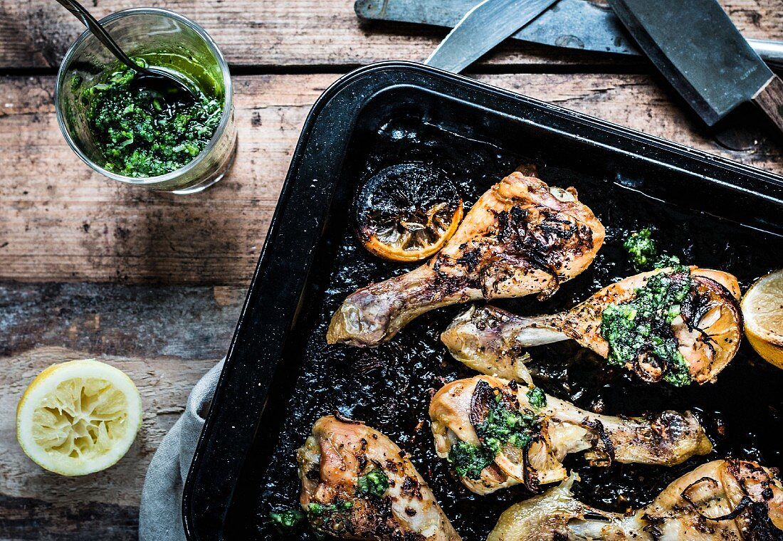 Lemon chicken legs with pesto on a baking tray