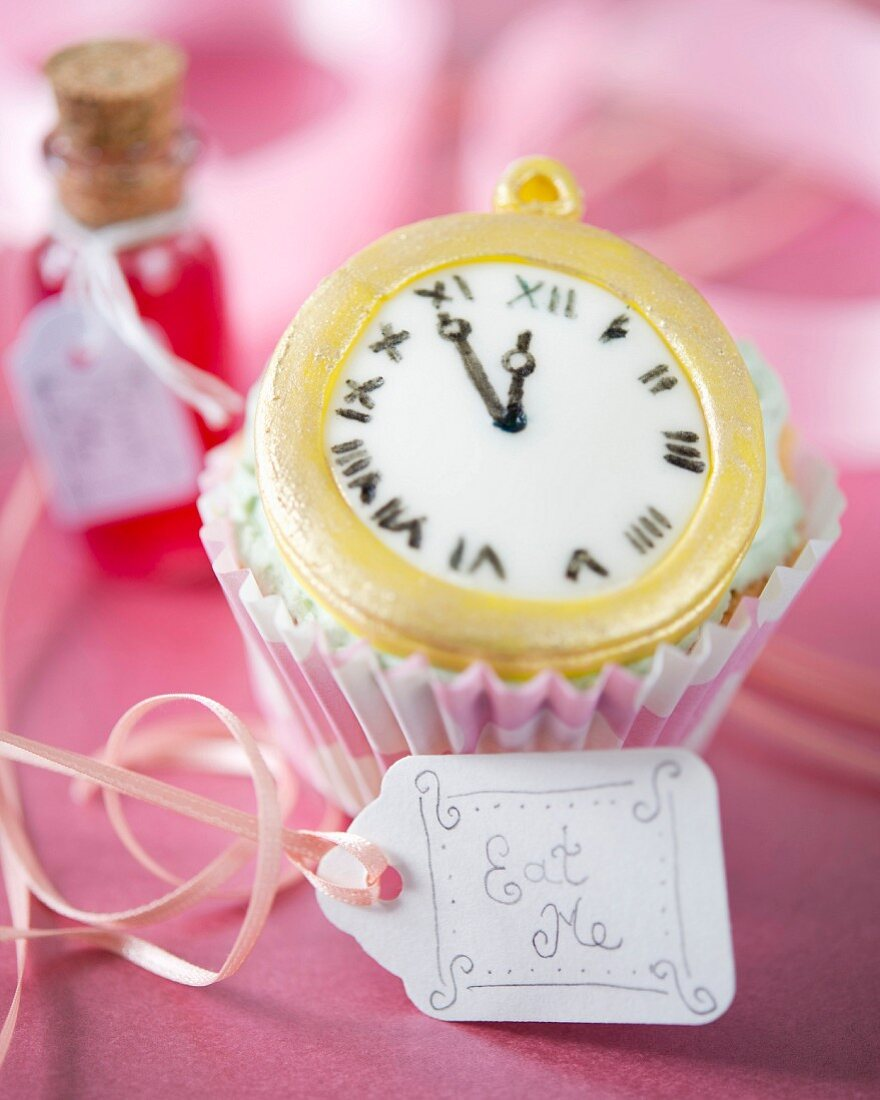 An Alice In Wonderland cupcake with a fondant clock