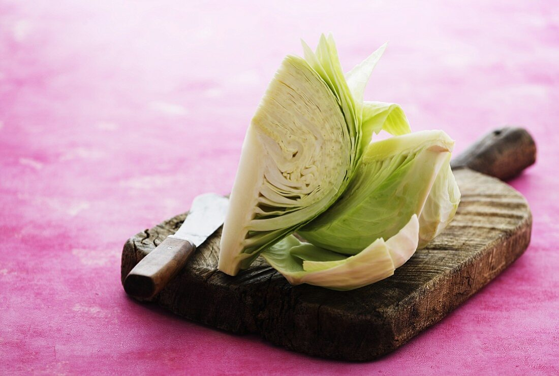 A quartered of a white cabbage on a chopping board