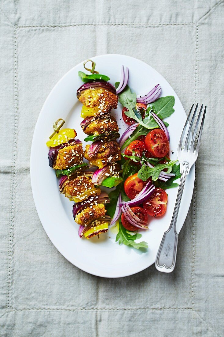 Spiced curry chicken and vegetable skewers with sesame seeds and tomato salad