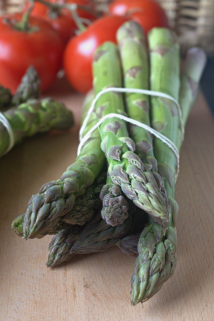Green asparagus and tomatoes on a wooden board