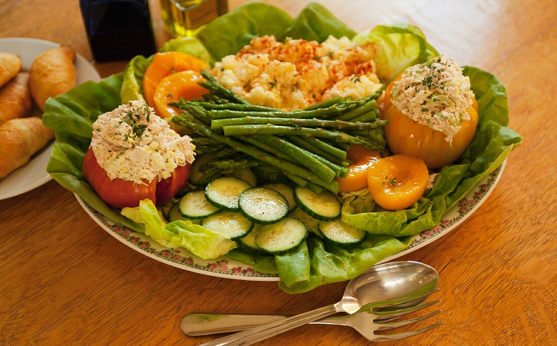 Tuna-stuffed tomatoes, and various vegetables on a serving platter