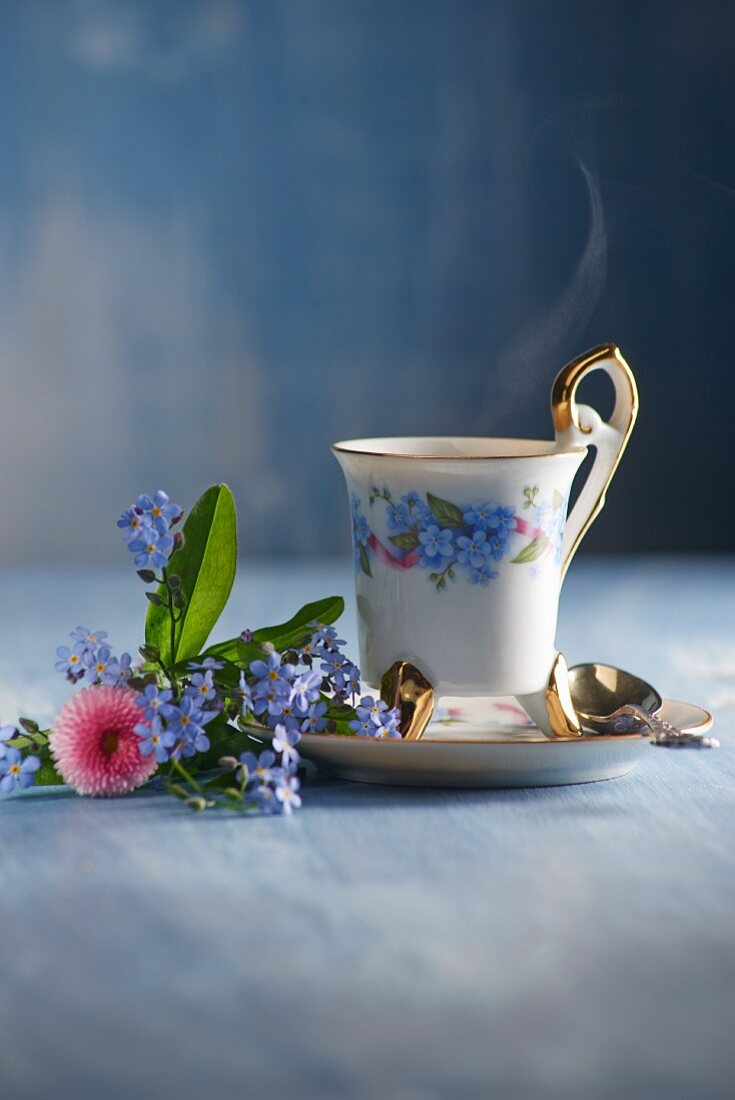 A steaming cup of coffee with a small bouquet of forget-me-nots and daisies
