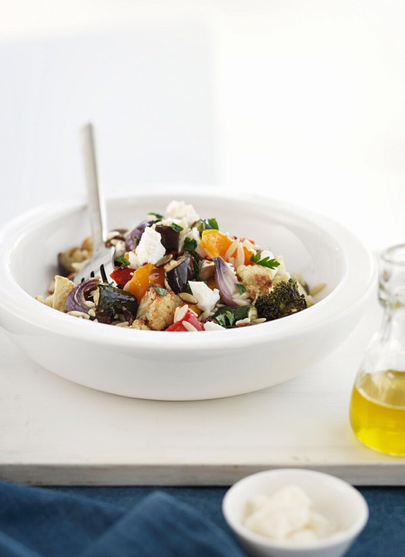 Oven baked vegetable salad with rice pasta and feta cheese