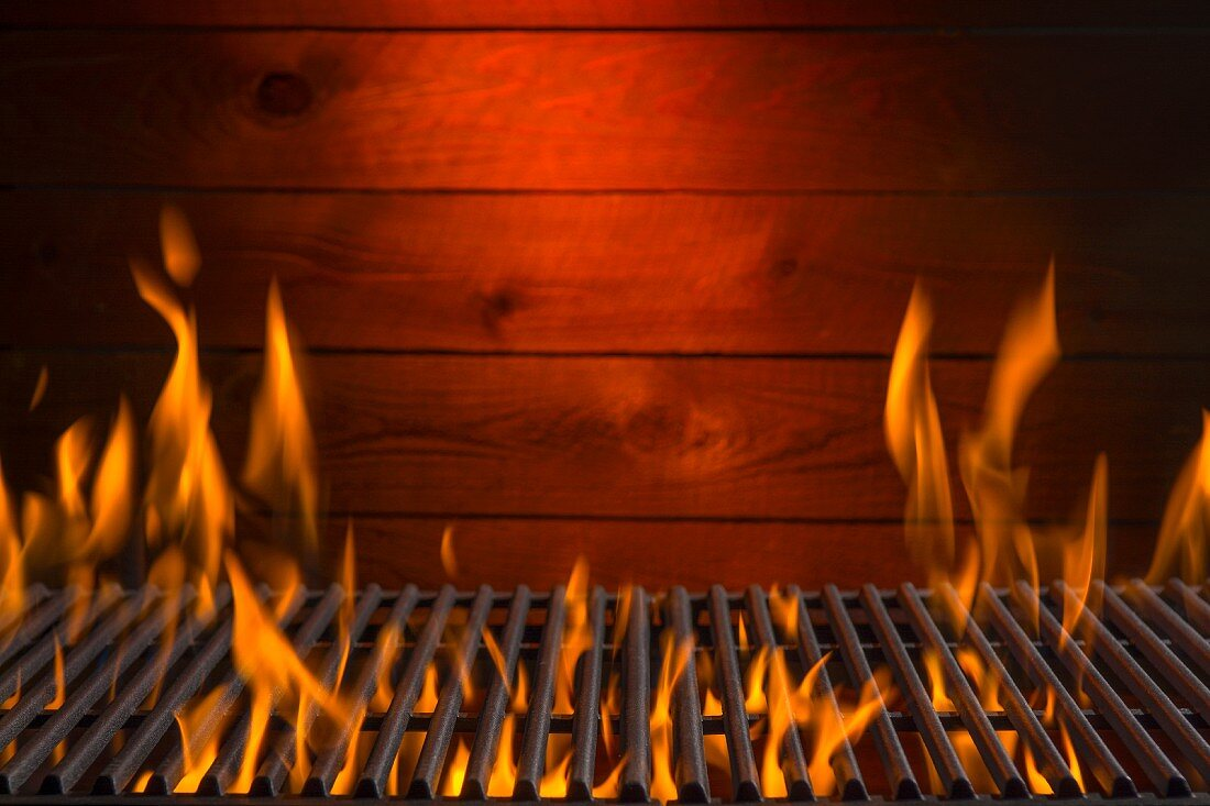 A flaming hot barbecue grill against a wooden wall