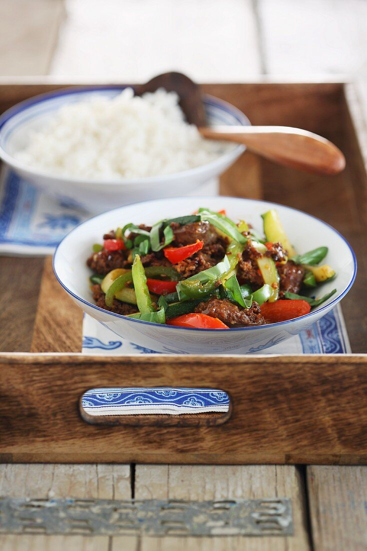 Oriental fried beef with vegetables and sausages