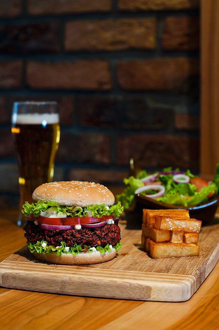 A hamburger, chips and a mixed leaf salad